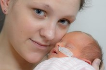 mum looks at camera holding baby to face nasal tubes