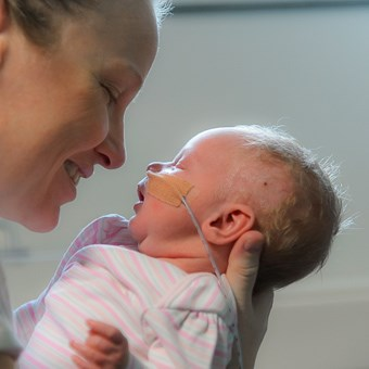 mum holds baby face nasal tube visible colour