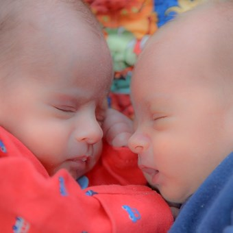 sleeping twins on blanket blue and red baby grows